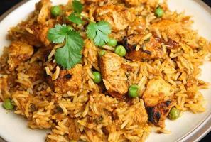köstliches indisches Huhn tikka biriyani auf weißem Teller foto