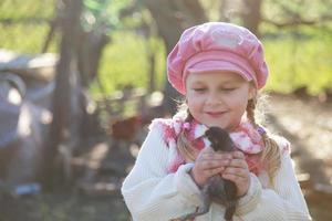 Mädchen hält Huhn im Freien foto