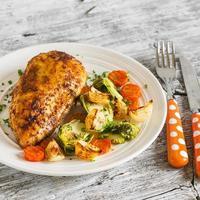 gebackene Hühnerbrust mit Rosenkohl, Zwiebeln und Karotten foto