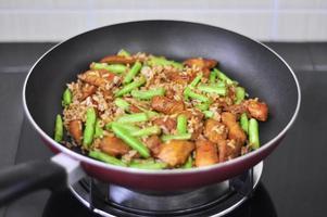 Huhn mit orientalischem gebratenem Reis der grünen Bohne in einer Pfanne foto