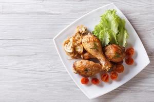 Hähnchenschenkel mit horizontaler Draufsicht von Pilzen und Tomaten foto