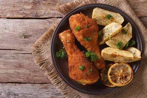 Hähnchenschenkel im Teig, mit Kartoffel auf Teller Nahaufnahme. oben foto