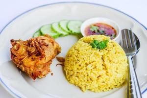 gelber Reis mit gebratenem Huhn auf Teller.