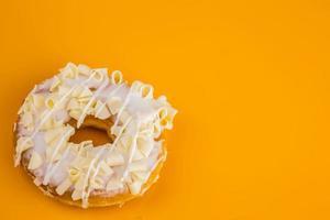 weißer Schokoladenkrapfen auf gelbem Hintergrund foto