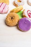 frische bunte Donuts auf weißem hölzernem Hintergrund, Nahaufnahme