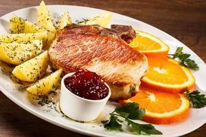 Schweinekotelett, Salzkartoffeln und Gemüse foto