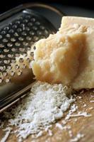 Block frisch geriebener Parmesan mit Käsereibe foto