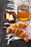 Croissants mit Honig im rustikalen Stil foto