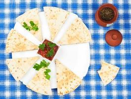 geschnittene Tortillas mit Basilikum auf Platte foto