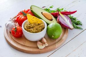 Guacamole und Zutaten - Avocado, Tomaten, Zwiebeln, Knoblauch, Limette