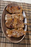 Gegrilltes Schweinefleisch im thailändischen Stil auf Holzteller