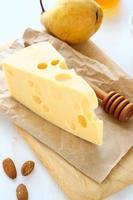 Käse mit Mandeln und Birne auf einem Schneidebrett foto