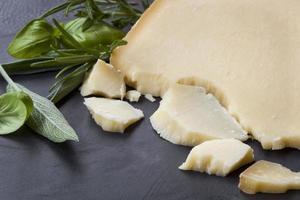 Gruyere-Käse mit Kräutern auf dunklem Schiefer foto