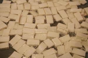 Nahaufnahme von festen Tofu-Quadraten, die in Öl braten foto