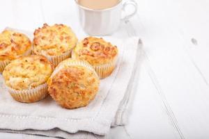 herzhafte Käse- und Speckmuffins auf dem weißen Tisch foto