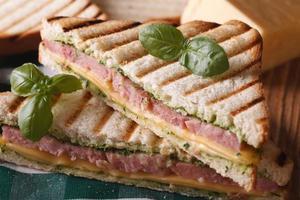 Gegrilltes Sandwich mit Schinken, Käse und Basilikum Nahaufnahme foto