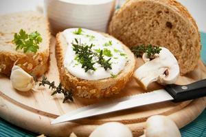 Brot auf Holzteller mit Frischkäse und Champignon foto