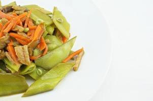 grüne Erbsen gebraten mit Karotten, Pilzen und veganem Eiweiß vegetarisch foto