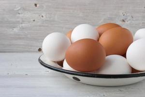 Hühnereier in einer Metallschale auf den weißen Brettern foto