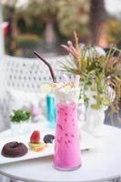 rosa Eismilch mit Schlagsahne auf dem Tisch foto