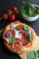 Pizza mit Mozzarella und Salami foto