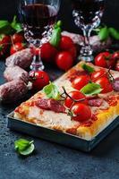 Pizza mit Salami und Tomate foto