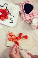 Studioaufnahme von Frauenhänden, die eine frische Erdbeere schneiden foto