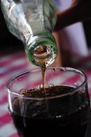 Glasflasche Cola wird in einen Becher gegossen foto