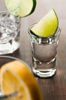 Schnapsglas mit Limettenkeil und klarer Flüssigkeit