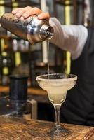 Barmann bei der Arbeit, Cocktails zubereiten. Margarita in Cocktailglas gießen.