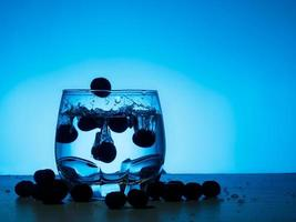 Blaubeere, die in Glas Gin fällt foto