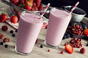 zwei gemischte Beeren-Joghurt-Smoothies in Gläsern mit Zutaten