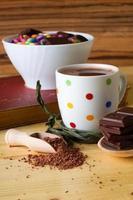 heißes Schokoladengetränk neben Schüssel mit Süßigkeiten