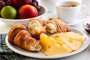 Croissants mit Käse, Obst und Kaffee