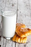 Glas Milch und zwei frisch gebackene Brötchen foto