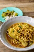 Thai-Nudel-Curry-Suppe mit Huhn auf Holztisch foto