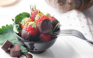frische Erdbeeren in dunkle Schokolade getaucht foto