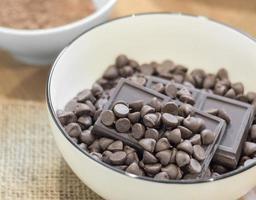 Schokoladenstückchen und dunkler Schokoriegel in weißer Schüssel. foto