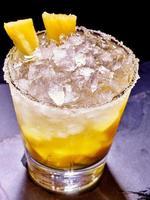 gelbes Würfeleis des kalten Getränks mit Ananas auf Dunkelheit