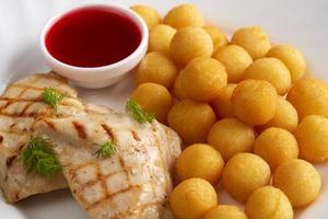 Gegrilltes Fleisch, Käsebällchen und Preiselbeersauce