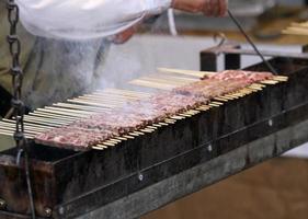 kochen Sie in mittelalterlicher Tracht, während Sie Fleisch kochen foto