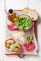 italienische Snacks. Salami-Sandwich mit Parmesan und breitem Bea foto