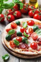 Italienische heiße Pizza mit Salami, Oliven und Tomaten foto