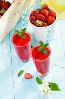 Erdbeer-Smoothie und Blütenblätter auf blauem Hintergrund foto