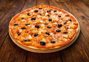leckere Pizza mit Ananas, Hühnchen und Oliven foto