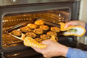 Frau, die frische Kekse aus dem Ofen nimmt foto