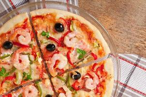 Pizza mit Garnelen, Lachs und Oliven foto