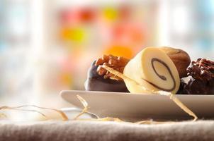 verschiedene Bonbons in weißer Schale und farbenfroher Hintergrundfront vi foto