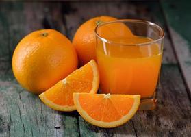 Orangensaftglas und frische Orangen auf Holz