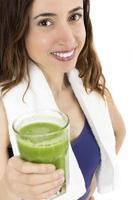 Fitnessfrau zeigt ein Glas Smoothie foto